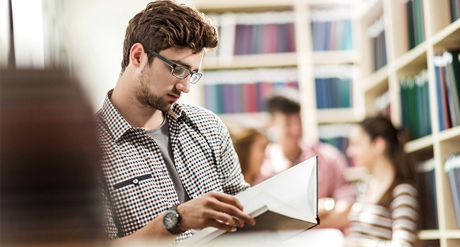 student teacher in library reading up on teacher requirements for his state