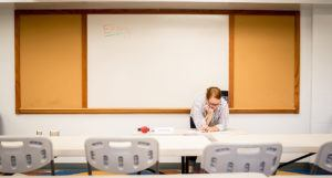teacher in empty classroom thinking about the teacher job market