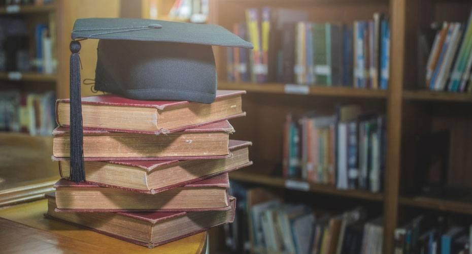 bachelors in education graduation cap resting on books