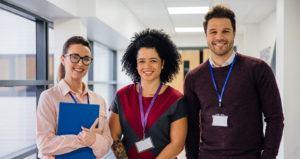 three teachers pose in a school hallway